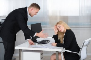 51090664 - boss shouting at female employee sitting at desk in office