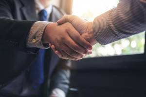 Two business men shaking hands during a meeting to sign agreemen
